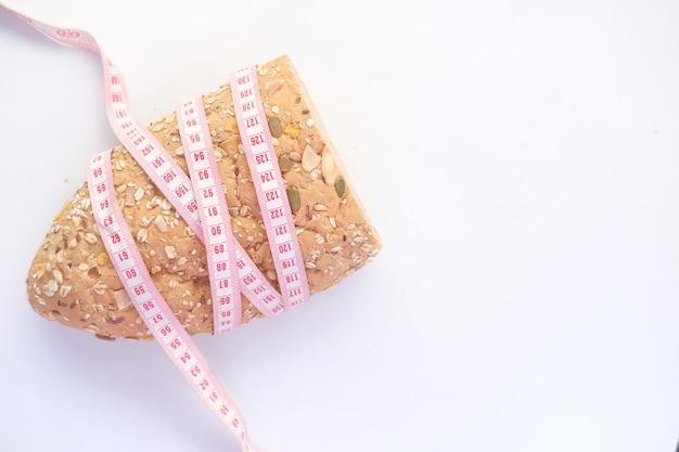 Sneetje volkoren brood en meetlint op witte achtergrond