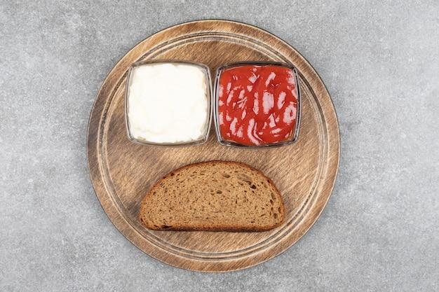 Sneetje zwart brood, ketchup en mayonaise op een houten bord