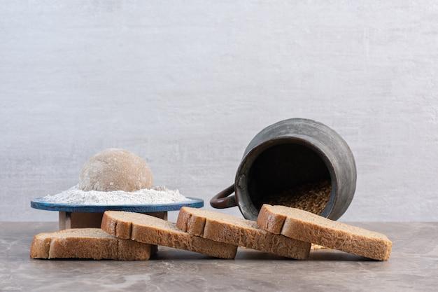 Sneetjes brood, bloemschotel en kruik tarwe op marmer.