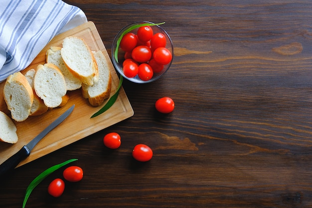 Sneetjes brood, brood of stokbrood op een houten snijplank, tafel. bij rijpe tomaten.