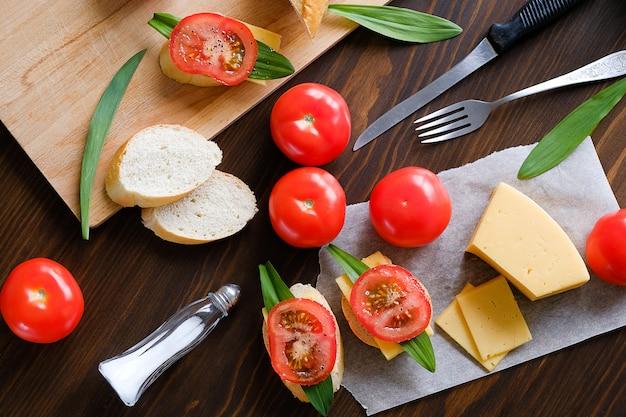 Sneetjes brood, broodjes, mes, snijplank, rode tomaten, zoutvaatje, kaas, groenen op een houten tafel, close-up. het concept van koken ontbijt of snacks, biologische producten van de boerderij. huis leven.