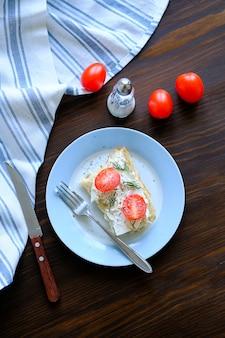 Sneetjes brood, broodjes, rode tomaten, kaas, groenen op een plaat. het concept van biologische landbouwproducten, kookschoolontbijt of lunches, snacks.