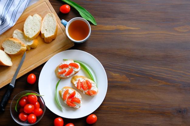 Sneetjes brood, broodjes, tomaten, kaas, op een bord. biologische landbouwproducten.