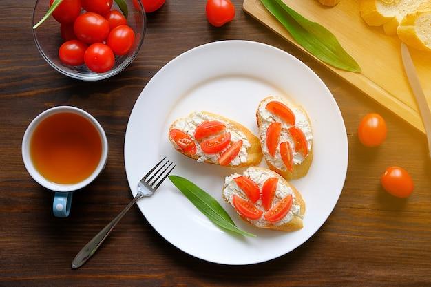 Sneetjes brood, een mok thee, broodjes met kaas en tomaten, groene slabladeren op een houten tafel. concept van biologische landbouwproducten. vegetarisme. selectieve aandacht.
