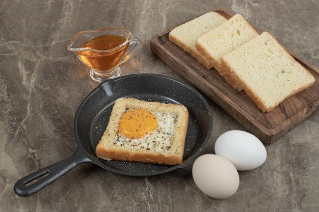 Sneetjes brood, eieren en olie op marmeren tafel. hoge kwaliteit foto