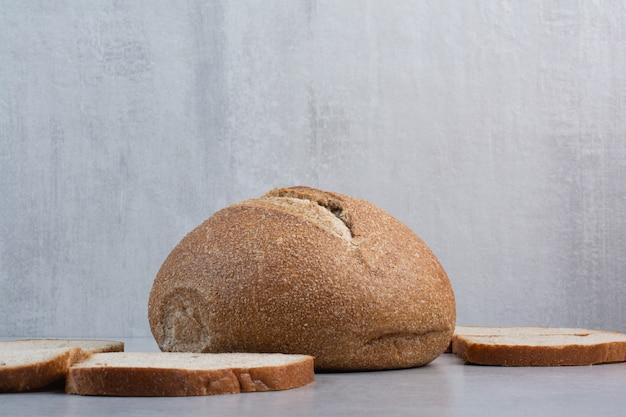 Sneetjes brood en heel brood op marmeren oppervlak
