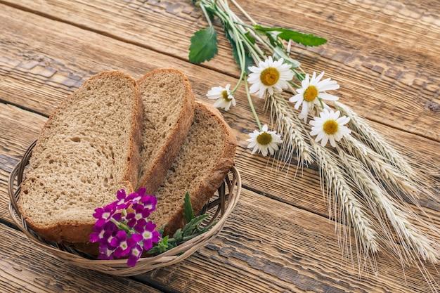 Sneetjes brood en verbena bloemen in rieten mand, kamille bloemen en droge aartjes van tarwe op houten planken. bovenaanzicht.