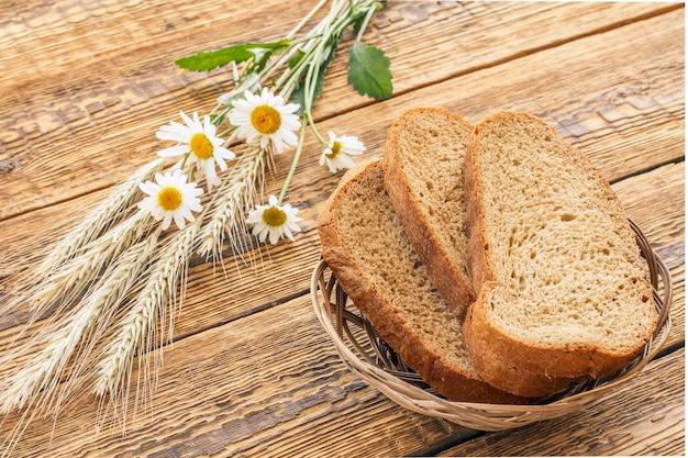 Sneetjes brood in rieten mand, kamille bloemen en droge aartjes van tarwe op houten planken. bovenaanzicht.
