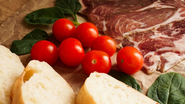 Sneetjes brood, kerstomaatjes, spinazie en ham. ingrediënten voor een broodje of bruschetta. gezond vers voedsel koken