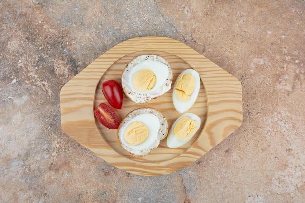 Sneetjes brood met gekookte eieren en tomaten op houten plaat