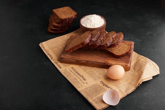 Sneetjes brood met ingrediënten op het stuk krant.