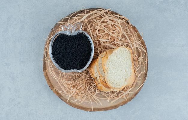 Sneetjes brood met zwarte kaviaar in een glazen beker.
