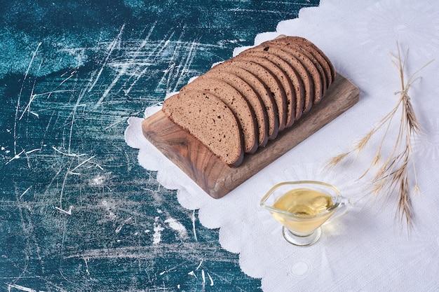 Sneetjes brood op een houten bord op blauwe tafel.
