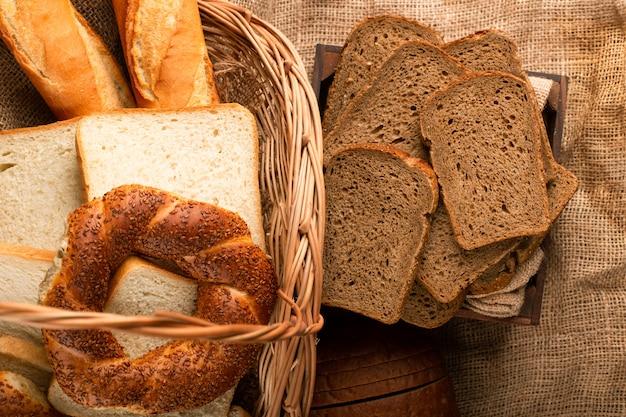 Sneetjes bruin brood in doos en bagels met stokbrood in mand