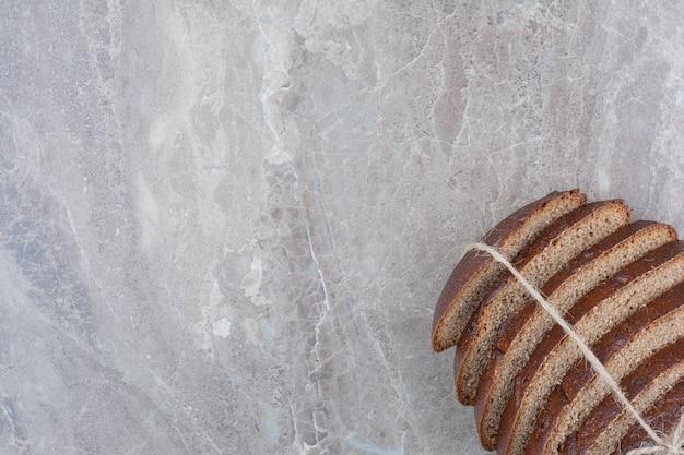 Sneetjes bruin brood in touw op marmeren oppervlak