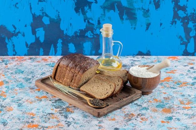 Sneetjes bruin brood met bloem en een fles olie op een houten bord.