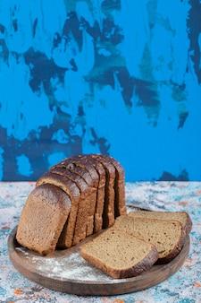 Sneetjes bruin brood met bloem op houten ronde bord.