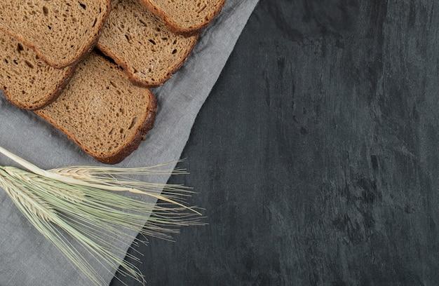 Sneetjes bruin brood met tarwe op een grijze achtergrond.
