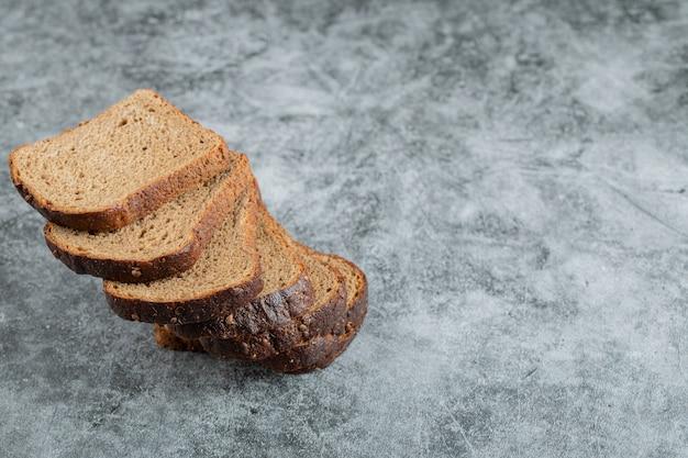 Sneetjes bruin vers brood op een grijze achtergrond.