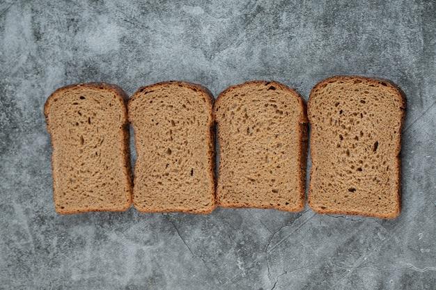 Sneetjes bruin vers brood op een grijze ondergrond.