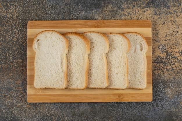 Sneetjes eigengemaakt brood op een houten bord.