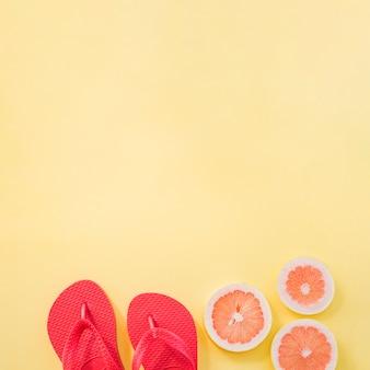 Sneetjes fruit in de buurt van slippers