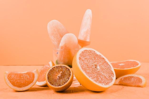 Sneetjes grapefruits en sinaasappels met ijslollys op een oranje achtergrond