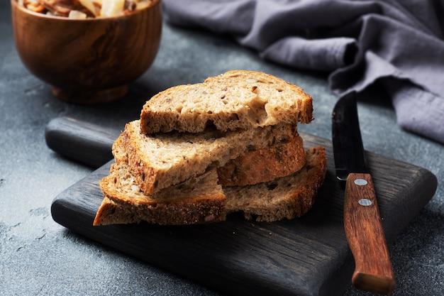Sneetjes volkoren brood op een houten snijplank. donkere concrete achtergrond.