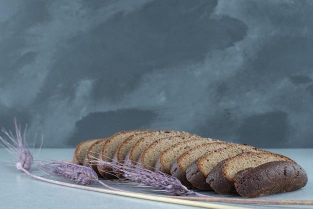 Sneetjes zwart brood op stenen tafel met tarwe