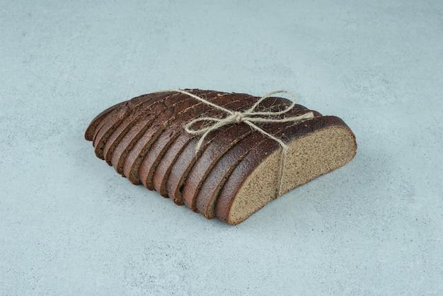 Sneetjes zwart brood vastgebonden met touw op stenen oppervlak