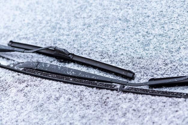 Sneeuw bedekt autoraam met wissers