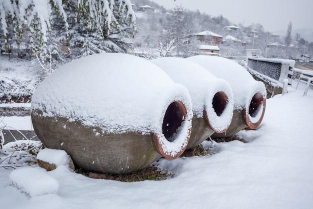 Sneeuw bedekt georgische kruiken voor wijn, buiten in de winter