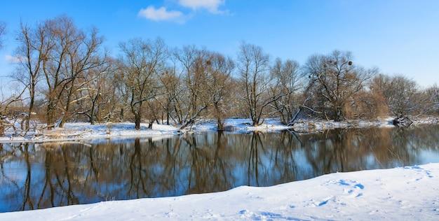 Sneeuw bedekte oever van kleine rivier tegen de blauwe hemel