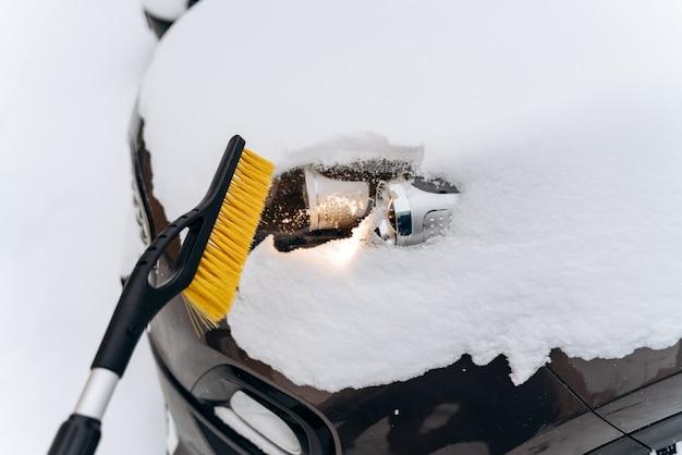 Sneeuw behandelde auto na blizzard. auto in de sneeuw na een sneeuwval in de stad. persoon die een speciale borstel gebruikt om het schoon te maken. winter en cyclonen concept. stock foto