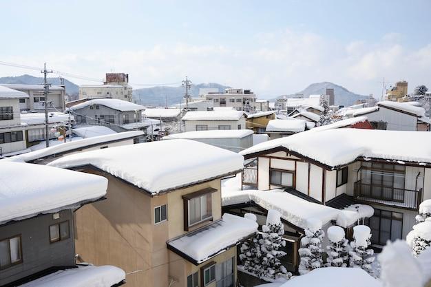 Sneeuw behandelde blokhuizen in dorpsplatteland als achtergrond, milieuconcept.