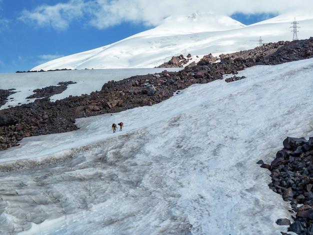 Sneeuw berglandschap van elbrus op een zonnige zomerdag. de twee reizigers klimmen op een besneeuwde weg in de berg.