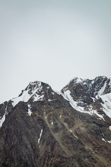Sneeuw bergtop in blauwe heldere hemel. rotsachtige rand onder wolken in zonnige dag.