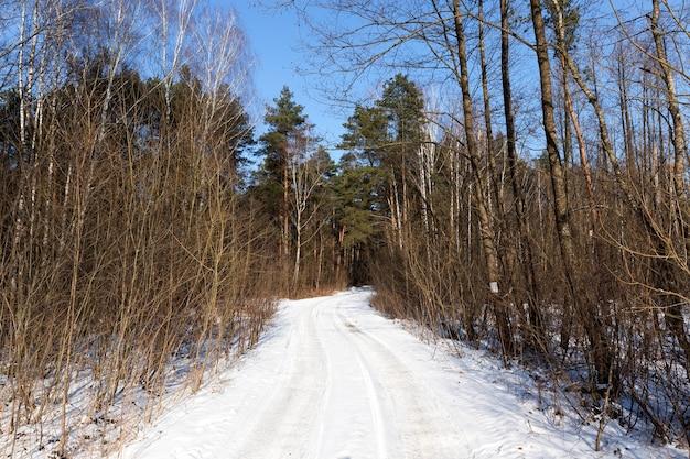 Sneeuw die viel tijdens een sneeuwval op de weg, weg in het winterseizoen, sneeuwval in het winterseizoen en de weg is niet geasfalteerd