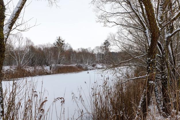 Sneeuw drijft op het meer, sneeuw drijft op het ijs van het meer na de laatste sneeuwval, bevroren meer in koud winterweer nadat de sneeuw viel