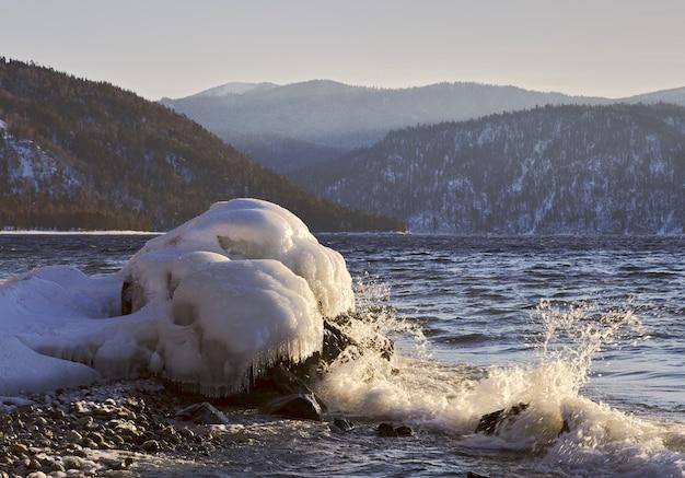 Sneeuw en ijs op de rotsen aan de oever van het teletskoje-meer dat in de winter niet bevriest