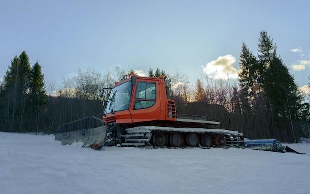 Sneeuw groomer machine op skispoor klaar om bij zonsopgang te werken