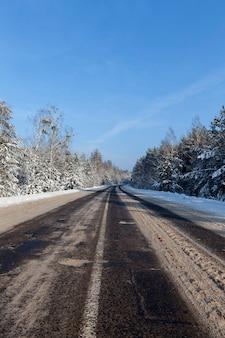 Sneeuw in de winter, sneeuw in ijzige winter met neerslag in de vorm van sneeuw, onderdeel van een besneeuwde winterweg