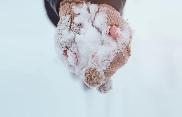 Sneeuw in handen die handschoenen dragen.