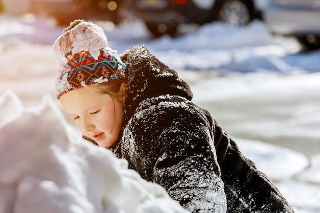Sneeuw op de oprit naar huis klein kaukasisch kind speelt buiten op besneeuwd