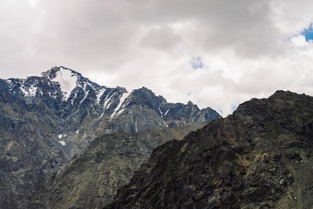Sneeuw op gigantische rotsachtige bergkam onder bewolkte hemel.