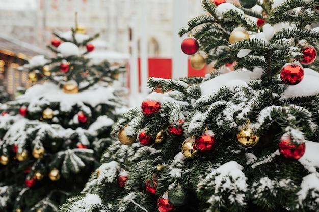 Sneeuw op takken van kerstbomen versierd met rode en gouden ballen op de straat van de stad. kerstmarkt.