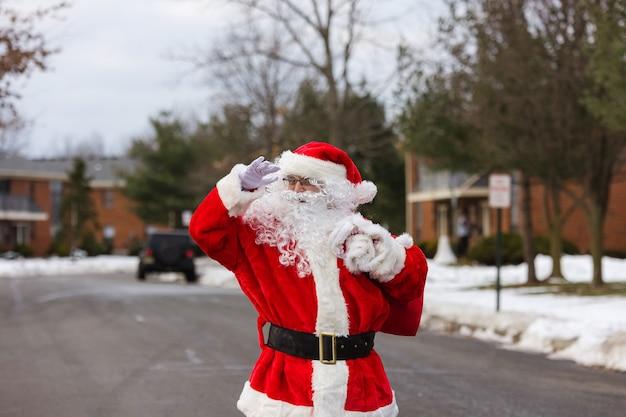 Sneeuw santa claus die langs de straat loopt, draagt een grote zak met geschenken op bomen die bedekt zijn met sneeuw