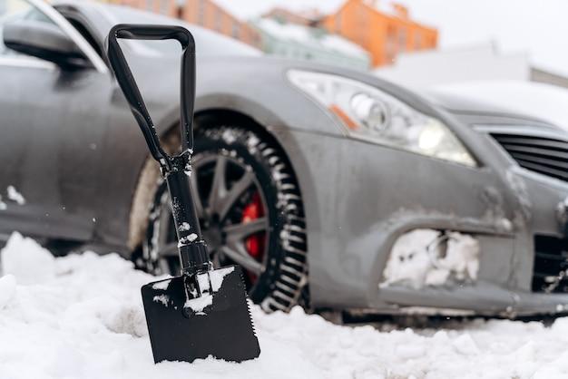Sneeuw verwijderen van auto. auto schoonmaken van sneeuwval. sneeuw op auto's na sneeuwval. winter stedelijke scène. auto bedekt met verse sneeuw. het proces van het reinigen van de auto van sneeuw