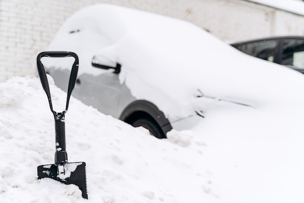 Sneeuw verwijderen van auto. schop staande op het eerste plan met auto op de achtergrond. sneeuw op auto's na sneeuwvalconcept