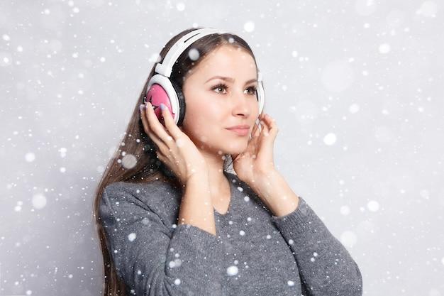 Sneeuw, winter, kerst, mensen, vrije tijd en technologie concept - gelukkige vrouw of tienermeisje in koptelefoon luisteren naar muziek van smartphone en dansen over sneeuw achtergrond